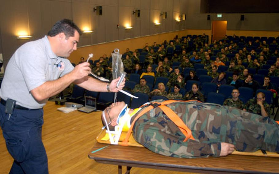 Joe McCluan, a teacher for the Florida-based Stay Alive From Education program, shows audience members a breathing apparatus as Senior Airman Lawrence Dojoles plays the role of a trauma victim during a presentation at the RAF Mildenhall theater.