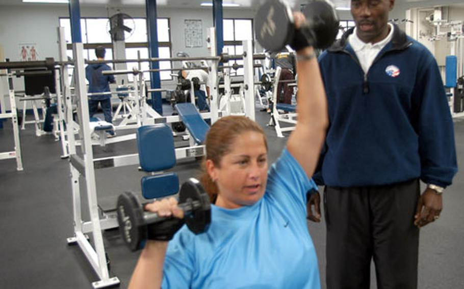 Personal fitness trainer Gilbert Moss spots Air Force spouse Jackie Alexander during a workout this week at the Potter Fitness Center.