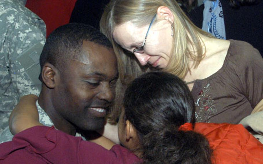 Sgt. Maj. Ivor Watson, secretary of the general staff sergeant major for V Corps' headquarters, shares a moment with his daughter, Leyna, and wife, Ellen, after returning Friday from nearly a year in Iraq with Heidelberg, Germany-based V Corps.