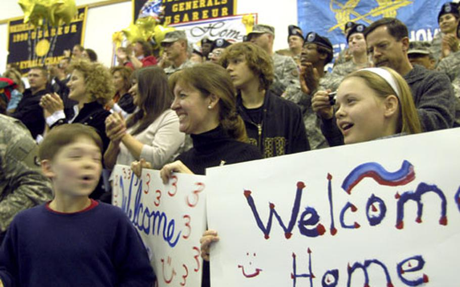 Charlie Fredrikson, 9, left, Kerah Fredrikson, center, and Kate Fredrikson, 11, hold signs welcoming home V Corps' Lt. Col. Chris Fredrikson as he marches into the gym at Patton Barracks Friday after almost a year in Iraq.