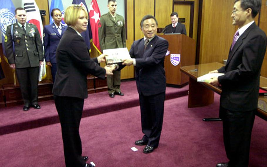 Petty Officer 1st Class Kathryn Remm accepts a holiday gift from South Korean Minister of Patriots and Veterans Affairs Park Yu-chul on Friday at Yongsan Garrison, South Korea.