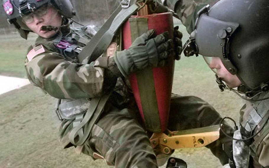 Wearing some of the newly-issued gear, Spc. Jose Rivera, a flight medic with the 236th Medical Company Air Ambulance, prepares to be lowered on a hoist operated by Spc. Federico Quinones, a crew chief also assigned to the 236th, Wednesday in Landstuhl, Germany.
