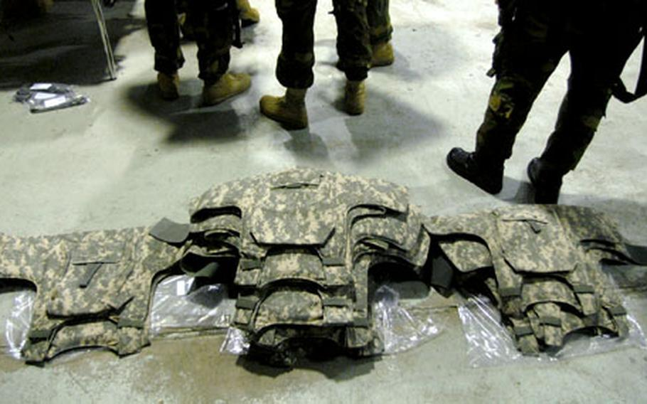 """New battle armor lies on the floor as aircrew from the 236th Medical Company Air Ambulance wait in line Wednesday to receive their new """"Air Warrior"""" life support equipment."""