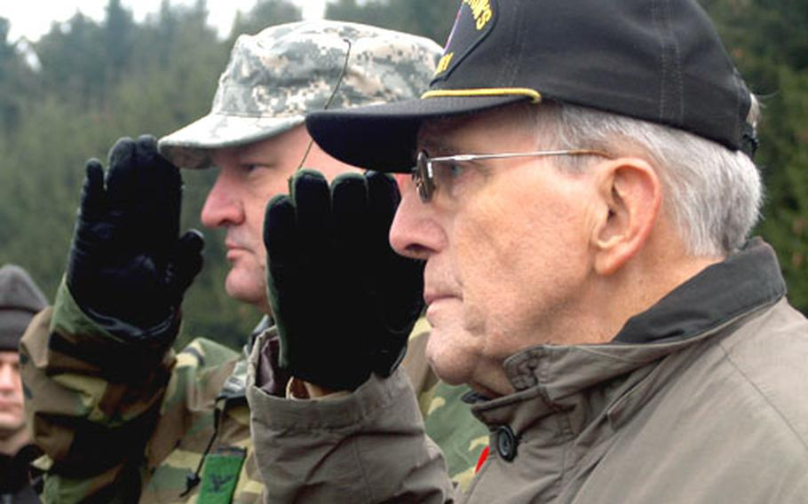 Col. Dean A. Nowowiejski, USAG Benelux commander, left, and Maurice Sperandieu, World War II veteran and founder of the annual march in Bastogne, salute during the ceremony at the 506th Parachute Intrantry Regiment monument.