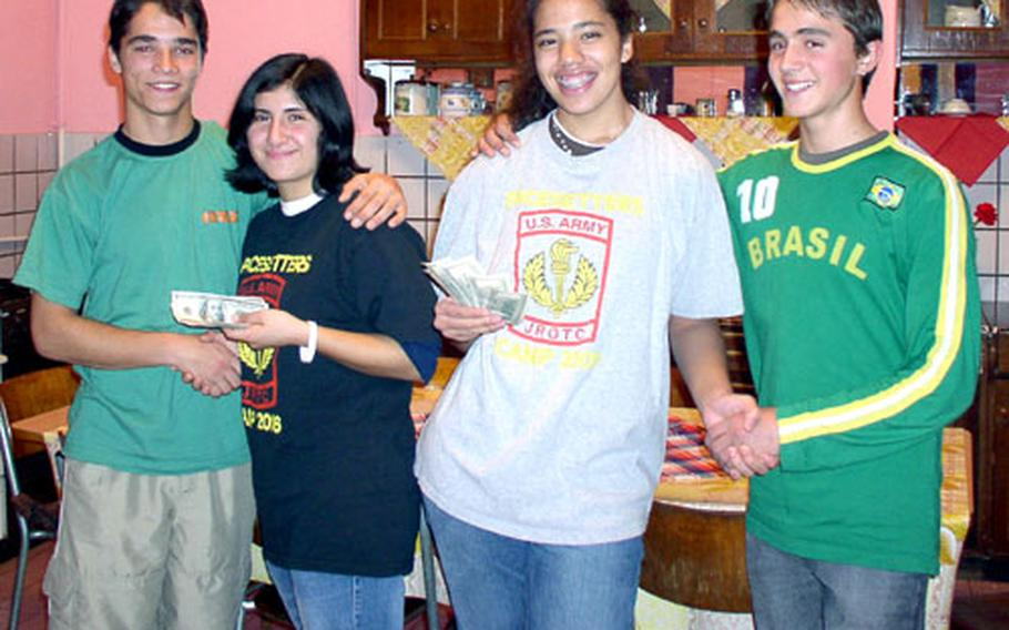 Patch High School students Jesi Perez, second from left, and Dani Thomas, second from right, smile with residents of a Santana, Romania, orphanage. The students raised $1,000 for the orphanage by bagging groceries at the commissary.