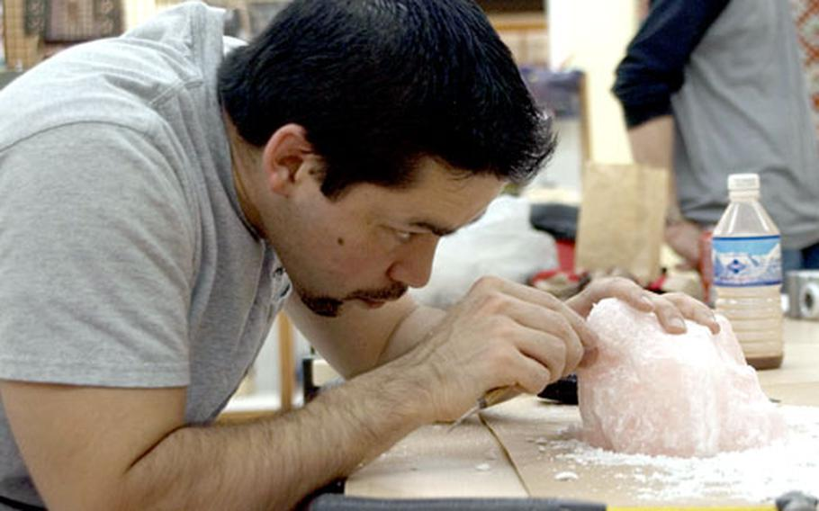 Ronald Miyashiro, a member of the U.S. Snow Sculpting Team, carves a section of the scale wax model of the sculpture the team will be creating during next year's competitions.