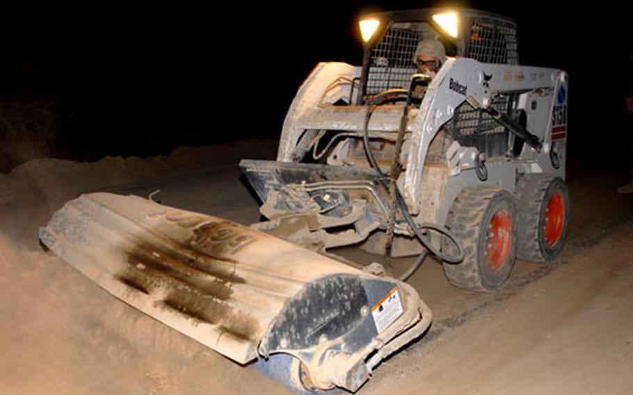 Marine engineers operate a bobcat Sunday during a mission to rid a stretch of major highway of hardpacked dirt, which is used by insurgents to hide improvised explosive devices.