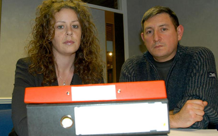 Attorney Sharon Allison and U.S. Air Force Tech Sgt. Brian Garcia sit behind a stack of files connected to Garcia's claim against the U.S. Air Force for medical malpractice. The Air Force settled the claim with Garcia, but did not admit negligence.