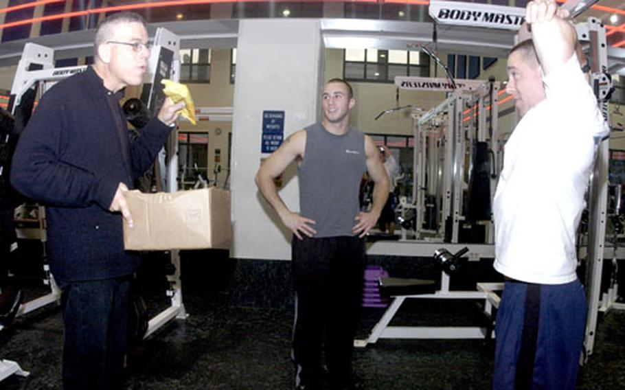 Chaplain (Lt. Cmdr.) Seth Phillips, left, invites a couple of single sailors working out at the base gym to join other single sailors at the Fellowship Hall on Saturday to partake of free fast food and a movie.