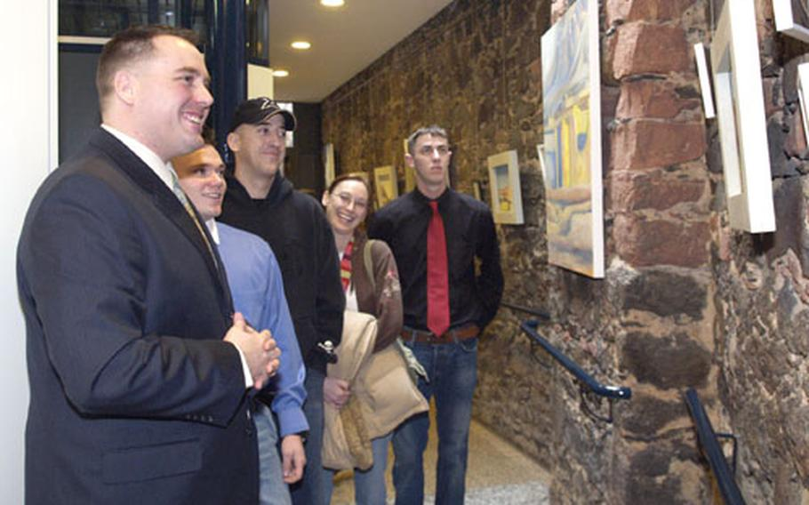 Colleagues of U.S. Army Spc. Mark Duran, left, survey an exhibition of his paintings of Afghanistan in downtown Hanau, Germany. Pictured with Duran, from left, are: Spc. Josiah May, Sgt. Larry Parker and his wife, Jessi, and Spc. Joshua Turner.