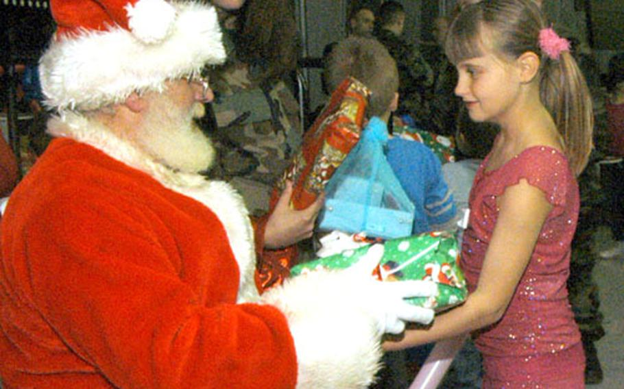 Dressed as Santa, Norman Killen, a British civilian with the 48th Equipment Maintenance Squadron, hands a gift to 8-year-old Skye Marsh inside the American Air Museum last week. Seventy local children were invited to attend a Christmas party sponsored by the maintenance squadron and the 48th Munitions Squadron.