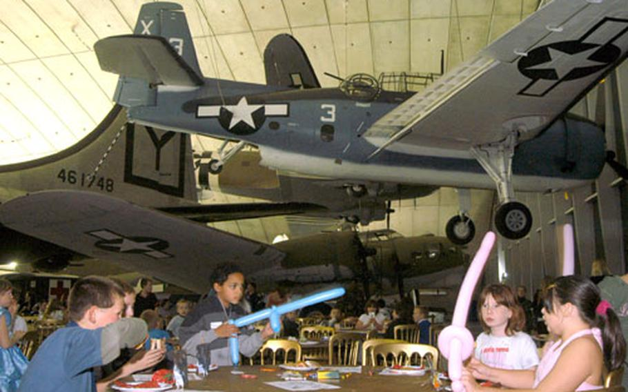 British children sit in the shadows of American aircraft of yesteryear during a Christmas party at the American Air Museum.