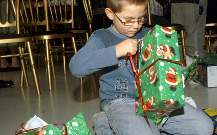 Eight-year-old Daniel Ventress unwraps his gift.