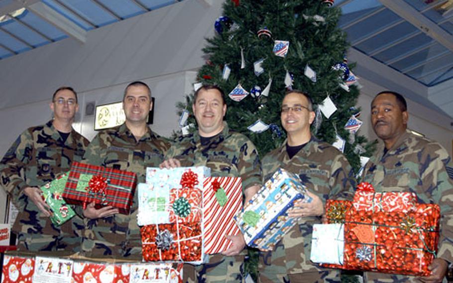 From left, Chief Master Sgt. Steve Dilda, Master Sgt. Andy Denham, Senior Master Sgt. John J. Dunham, Senior Master Sgt. Robert Loftus and Master Sgt. Larry Haynes, hold gifts donated as part of the Angel Tree program.
