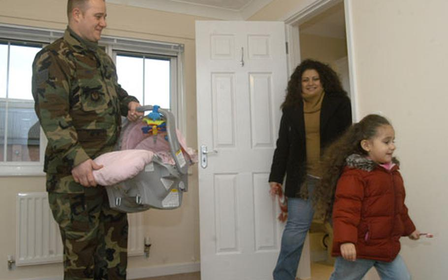 Staff Sgt. John Vohs, left, holds his 8-week-old daughter, Vannessa, as his other daughter, Alisha, 3, and wife, Brenda, tour a bedroom in their new home on Dec. 13.