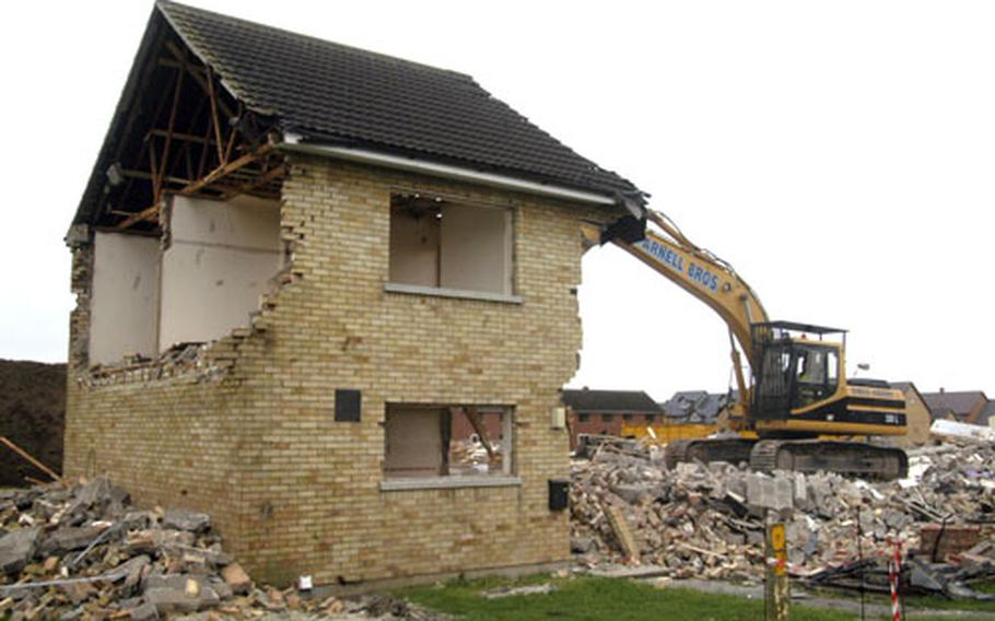 An excavator demolishes an old home as part of the ongoing five-year Liberty Housing Village project.