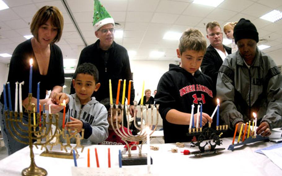 """Isaiah Branch, 5, left, and David McCormick, 10, light Hanukkah menorahs Tuesday evening as Rabbi (Lt. Cmdr.) Seth Phillips, wearing the Christmas tree hat, instructs them on the process and meaning of the Jewish """"festival of lights."""""""