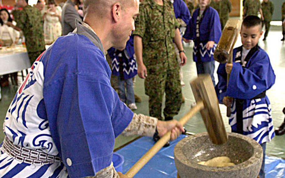 Col. James Adams, with 1st Marine Aircraft Wing, and his son William, 8, pound rice into a paste used to make mochi, a Japanese rice cake traditionally eaten during the new year season, at the Japanese Ground Self-Defense Force's 2006 Rice Pounding Ceremony at Camp Naha, Okinawa, on Wednesday. William said the mallet was heavy, but it was fun to swing and he planned to try some of the mochi balls he helped pound.
