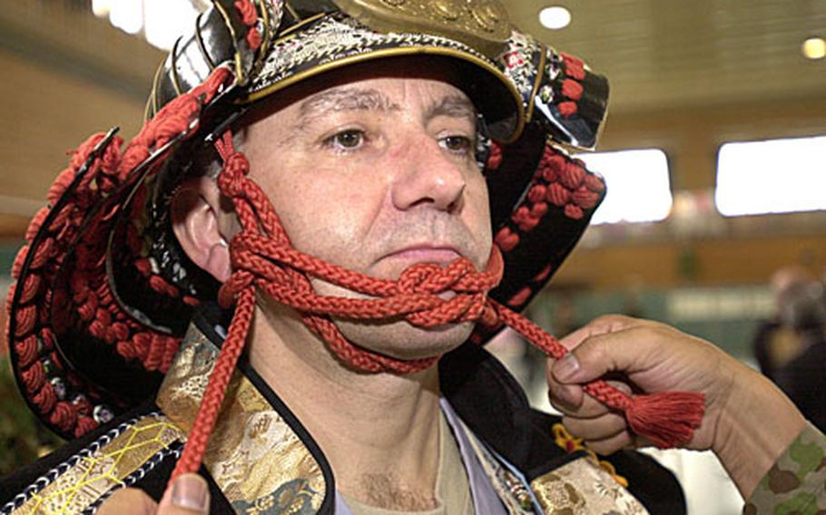 """Army Lt. Col. Timothy Tuckey, with the 10th Army Support Group, gets strapped into a samuri helmet and the rest of the samuri outfit at the 2006 Rice Pounding Ceremony. Of wearing the samuri outfit, Tuckey said, """"It's more comfortable than Army body armor."""""""