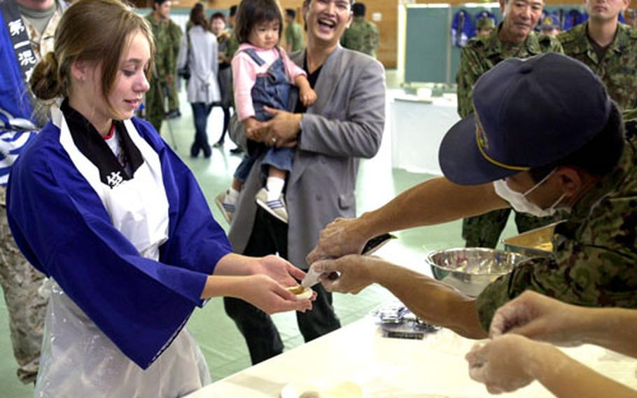 Hannah Soule, 13, the duaghter of a Marine captain, tries her hand at rolling a mochi ball at the 2006 Rice Pounding Ceremony. Soule said she didn't know what was being put in her mochi, but it was OK since her dad was going to eat that one.