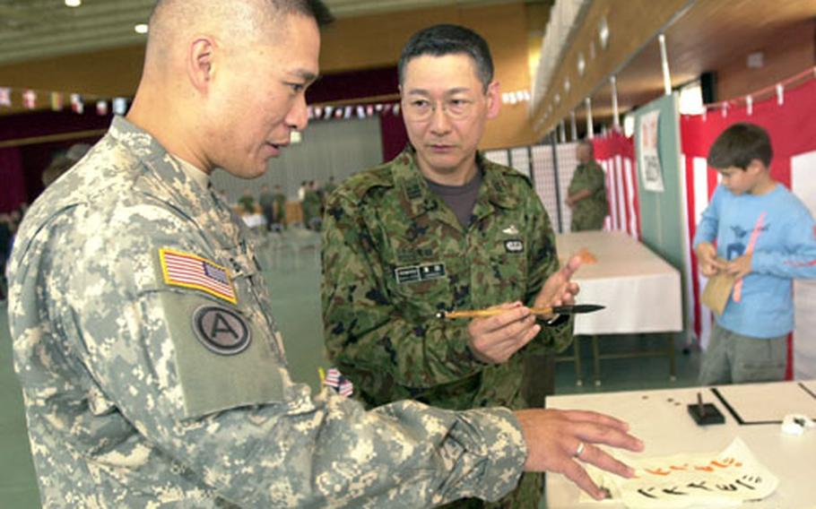 """Army Maj. Roy Banzon, left, with the 505th Quartermaster Battalion, listens as Japanese Ground Self-Defense Force Lt. Col. Taneo Hamada, a dentist with 1st Combined Brigade, explains that the symbols he used to write Banzon's name in calligraphy could also be translated as """"much respect."""" Banzon, who plans to frame the parchment, said, """"I didn't realize that was what (my name) meant."""""""