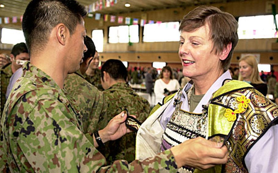 """Maj. Gen. Mary Ann Krusa-Dossin, commander of Marine Corps Base Camp Butler, tries on a samuri outfit. In her opening remarks at the ceremony, Krusa-Dossin said the event was a """"wonderful experience, especially for those of us new to the island"""" and that the American and Japanese militaries based here need more such cultural exchanges."""