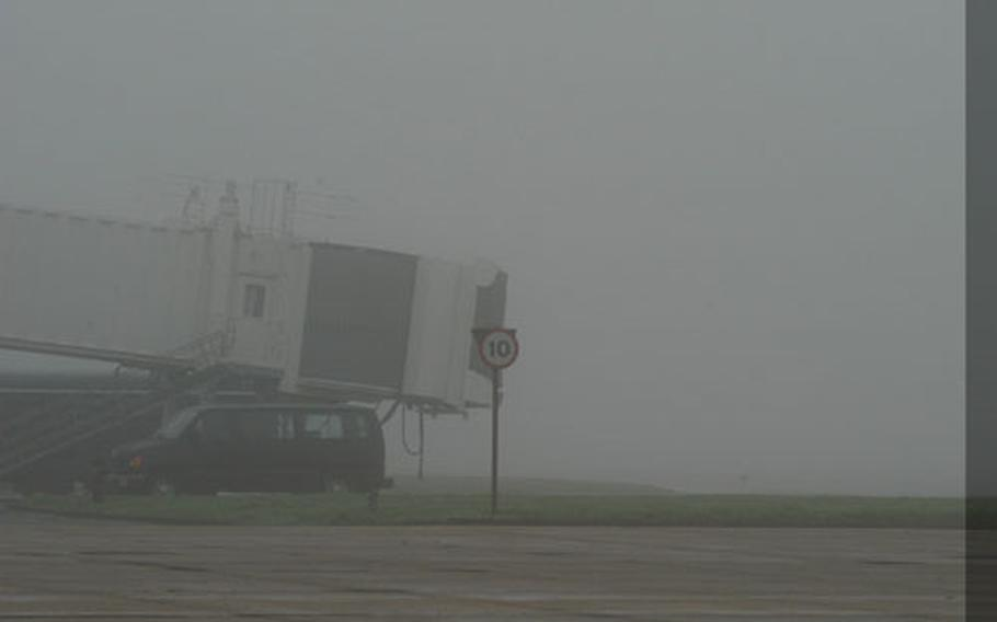 The jetway at the RAF Mildenhall, England, passenger terminal sticks out of the thick fog that has shrouded much of England for several days. The diminished visibility caused delays at airports across the country.