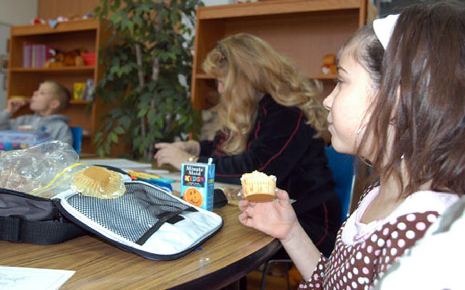 """Autumn Newpher eats a cupcake during """"Lunch Bunch"""" with counselor Leigh Fox and other students."""