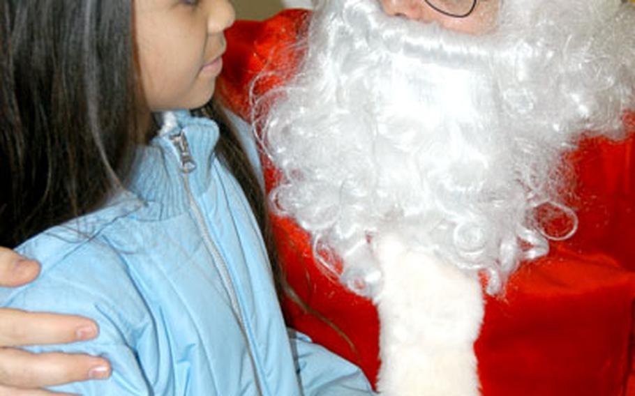 """Myriam Huertas, 10, tells Santa Claus her Christmas wishes during a recent event at the Airman and Family Readiness Center at Misawa Air Base, Japan, for students who have a parent deployed. Myriam, who participates in """"Lunch Bunch"""" at Sollars Elementary School along with two of her sisters, said she told Santa she wanted her mom to come home. Master Sgt. Teresa Huertas is deployed and Myriam's dad, Tech. Sgt. Eliezer Huertas, will soon deploy."""