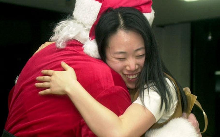 A teacher gets a big hug from Santa Claus Friday night at the Young Nak orphanage in Seoul. Servicemembers distributed more than 100 gifts at the Noncommissioned Officers Association-sponsored volunteer event.