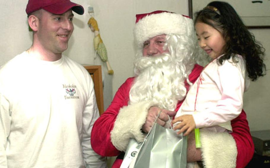 First Sgt. Jayson DeWitt, left, helps Santa Claus deliver a gift at the Young Nak orphanage.