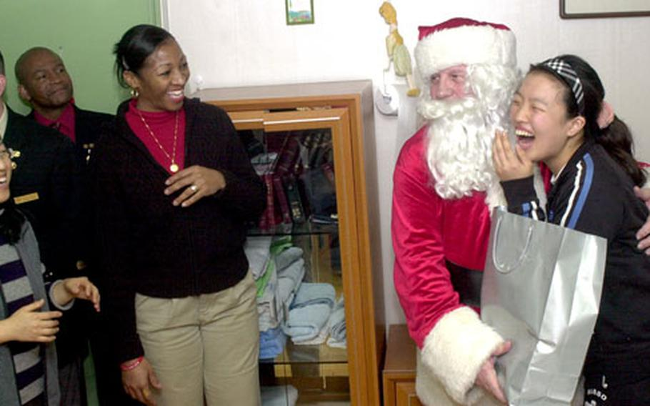 Air Force Master Sgt. Annie Hollings, left, assists in the gift distribution.