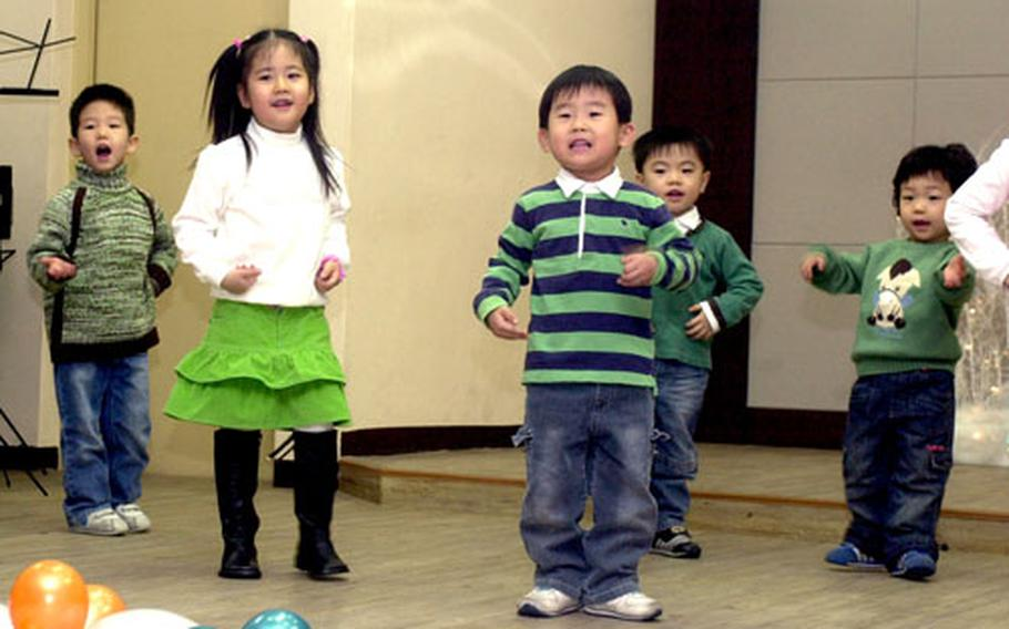 The youngest children at Young Nak orphanage in Seoul perform a Christmas dance routine for servicemembers who came to distribute gifts Friday night.