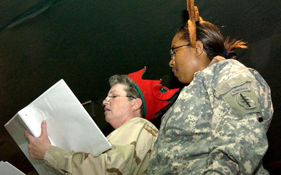 Navy Master Chief Petty Officer Teresa Carroll, of Klamath Falls, Ore., left, and Army Maj. Michelle Hines, of Wilmington, N.C., sing Christmas carols at Camp Lemonier in Djibouti on Friday.
