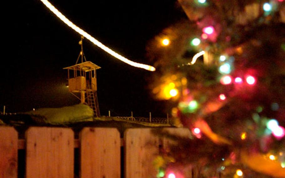 A Christmas tree and lights frame a guard tower at Camp Lemonier in Djibouti.