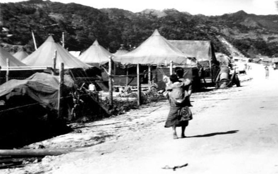 A barefoot mother carries her child past rows of refugee tents on Okinawa in 1945. The photo is one of a box full of photographs donated to an Okinawa historical society by American veteran Robert Rock.