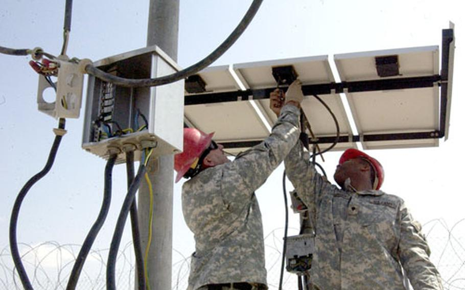 Damaged control boxes dangle from wires as Sgt. Bruce Weckman, 46, of Pratville, Ala. (right) and Spec. Alonzo Henderson, 20, of Montgomery, Ala., remove a damaged solar cell from a remote well and pumping station in Djibouti on Saturday.