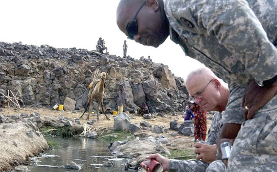 Staff Sgt. Richard Provitt, standing, and Sgt. Major William Lee inspect a spring-fed oasis near the border of Ethiopia in Djibouti as a group of nomadic tribesmen observe them from a distance Saturday.