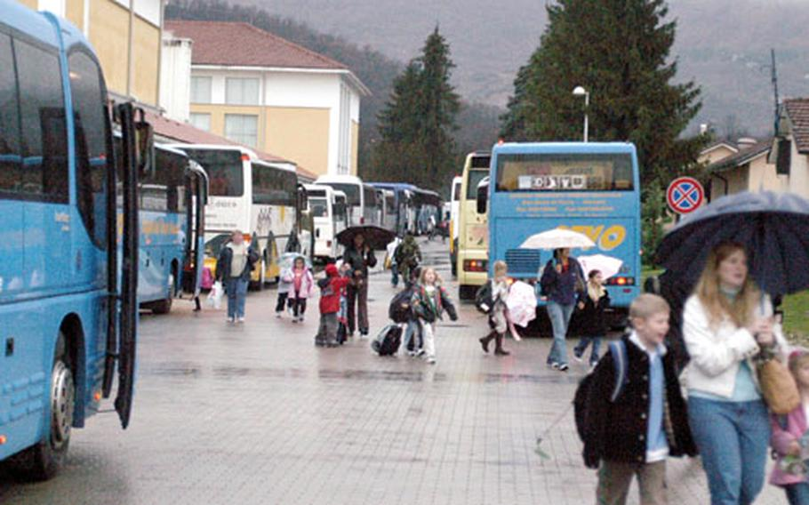 Parents and children walk by buses lined up after school on a rainy afternoon at Aviano Air Base, Italy.
