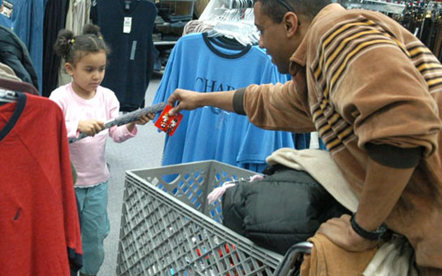 Five-year-old Artika White helps her dad, Arthur White, shop Tuesday at the post exchange in Wiesbaden, Germany. The store was clogged with shoppers seeking post-Christmas sales.