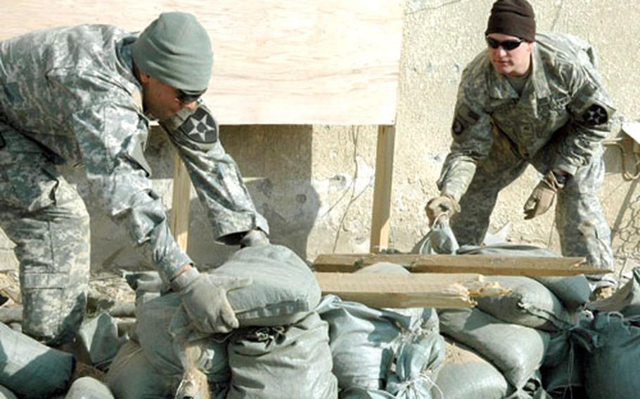 Sgt. Israel Arroyo, 22, left, of La Puente, Calif., and Sgt. Luke Draper, 25, of Long Beach, Calif., stack sandbags to protect a window shattered during a mortar attack on Forward Operating Base Loyalty.