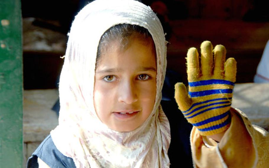 An Iraqi schoolgirl waves at the camera during class at the primary school adopted by 9th Engineer Support Battalion. There is no power in the building, so most of the children wear tattered gloves and hats to stay warm during their lessons. The Marines plan to hook up a generator so the school can have heat.