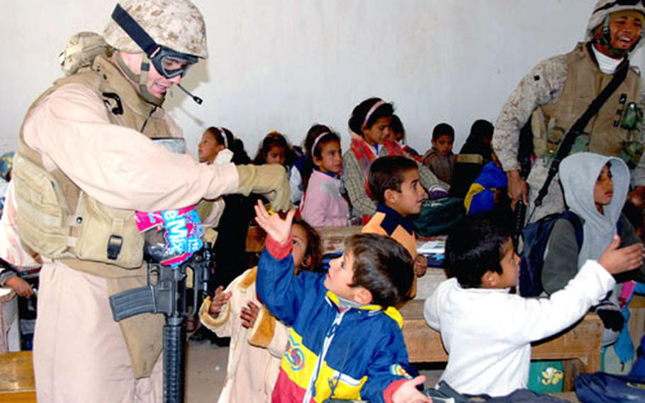 """Marine Gunnery Sgt. Steven Burkett, left, tries to hand out candy in an orderly fashion — one piece at a time — as Lance Cpl. An'Tion Aikins smiles at the kids. """"Sometimes you don't realize the impact you're making, but at the school you could see it on their faces,"""" Burkett said. The system soon broke down when some of the older boys from the neighborhood — who are too old for the primary school — took one of the candy boxes and started throwing handfuls to the class."""