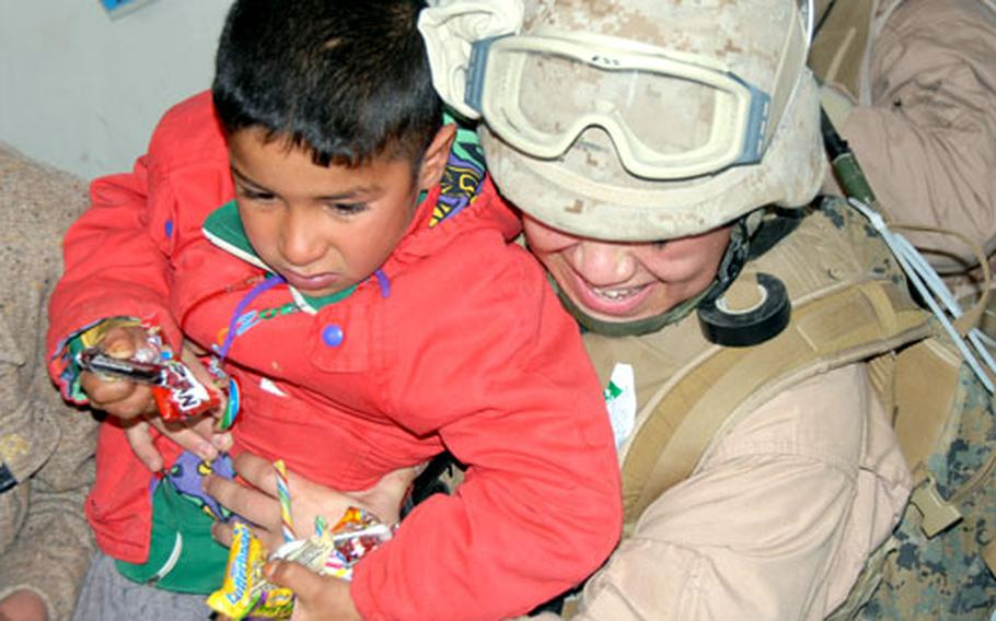 Lance Cpl. Anna Perez lifts an Iraqi schoolchild away from the candy box on the floor after candy chaos broke out in the classroom. The excited children couldn't get enough. The 9th Engineer Support Battalion Marines will be making regular stops at the primary school to do improvement projects. On Tuesday they dropped off newly built wooden desks and soccer goals. Next, they'll tackle the electricity.