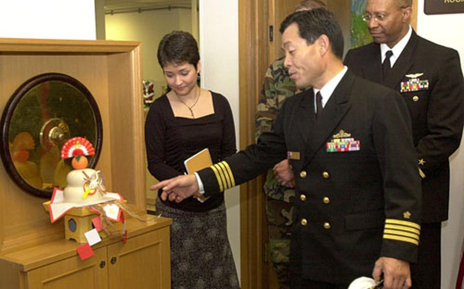 """Akira Akehi, commander for Japanese Maritime Self Defense Force White Beach Sub-Area Activity, explains the significance of the dried squid on the kagami mochi presented to the sailors at the headquarters for Commander Fleet Activity Okinawa Wednesday. Dried squid was used because """"it is chewy like gum,"""" he said. It takes a long time to eat it and that symbolizing having plenty to eat throughout the new year."""