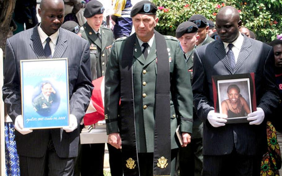 Army Chaplain (Maj.) Mark Nordstrom leads the funeral procession for Pfc. Lena Karungi, in Mbarara, Uganda on Nov. 12. Holding the photo of the V Corps soldier, who was killed in a train accident near Heidelberg in October, is a worker for the local funeral service.
