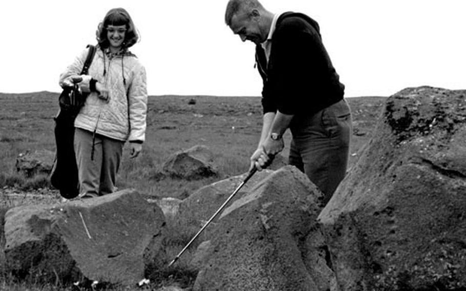 Caddy Sandy Emmert waits as CPO John E. Emert chips out from between some of Iceland's volcanic boulders.
