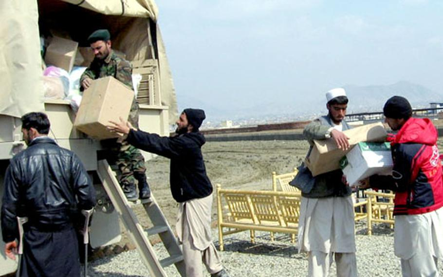 An Afghan National Army soldier helps load a truck with the boxes of donated clothing to distribute to an orphanage in an isolated part of the country about four hours from the base.