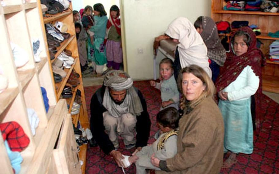 Children at the Wardak Province Orphanage in remote Afghanistan get fitted with shoes. Some of the donated clothes were taken the almost four-hour drive from Camp Phoenix to the orphanage, which is about 9,000-feet high in the mountains.