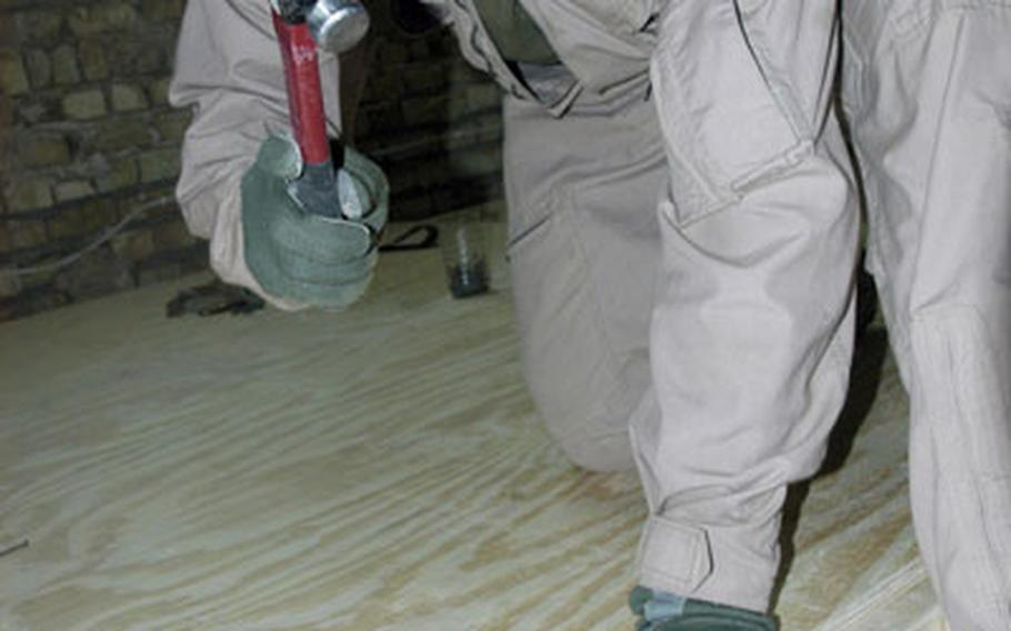 Combat Engineer Lance Cpl. Chris Houser, 25, of Providence Forge, Va., pounds nails into a floorboard that will serve as a sleeping area for soldiers living and working out of Out Post 3 in Karmah, Iraq, greatly improving the soldiers' living conditions.